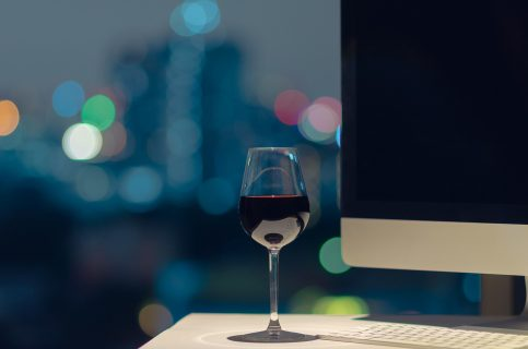 A glass of red wine put on working table, computer screen and keyboard with bokeh of city lights.